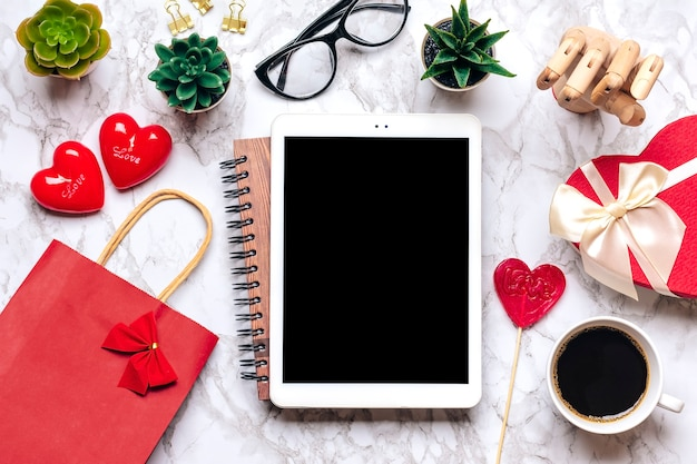 Tablet for chooses gifts, makes purchase, cup of coffee, debit card, box, bag, two hearts on marble table Premium Photo
