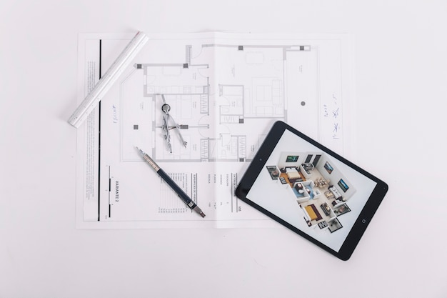 Tablet and drafting tools on blueprint Free Photo