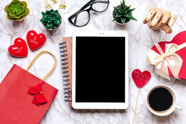 Планшет для выбора подарков, совершения покупок, чашки кофе, дебетовой карты, коробки, сумки, двух сердечек на мраморном столе Premium Фотографии
