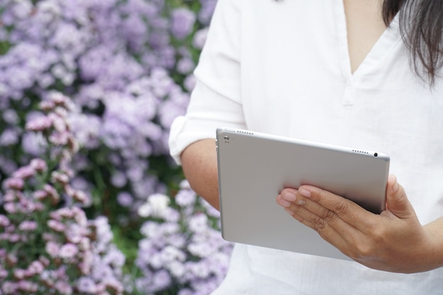 Таблетка в руках женщины, ученый, наблюдающий за фиолетовыми цветами растений. Premium Фотографии