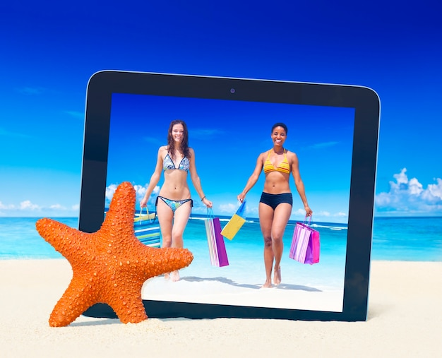 Tablet pc taking photo of women with shopping bags on a tropical beach. Free Photo