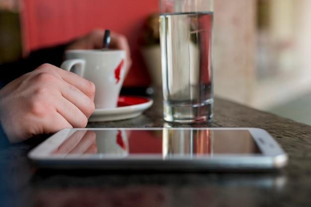 飲み物が付いているコップの近くのテーブルに置かれたタブレット 無料写真