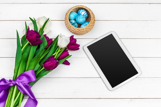 Tablet screen for message and colorful tulips and easter eggs on wooden Premium Photo