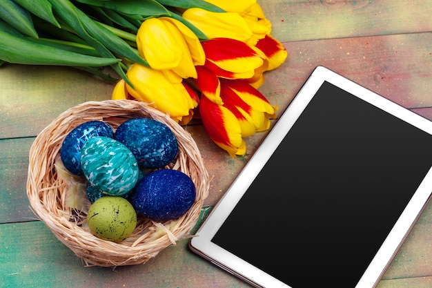 Tablet screen for message and colorful tulips and easter eggs Premium Photo