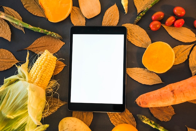 Tablet on table with vegetables Free Photo