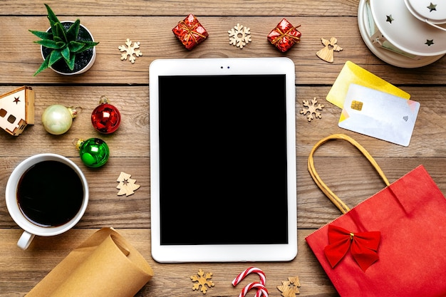 Tablet with black screen, cup of coffee, debit card, xmas decor, snowflakes on wooden table Premium Photo