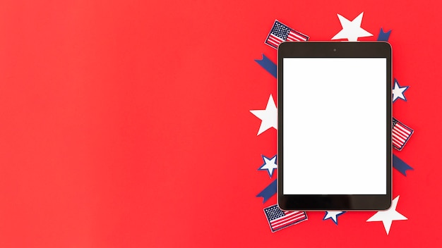 Tablet with decorative elements of american flag on red surface Free Photo