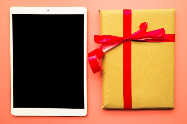 Tablet with gift box on table Free Photo