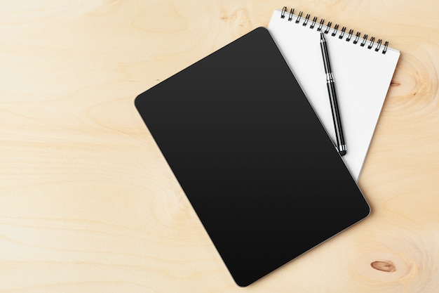 Tablet with notepad on wooden Premium Photo