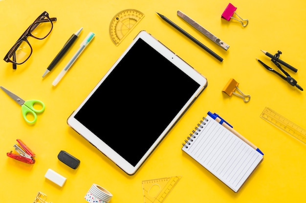 Tablet with office accessories on table Free Photo
