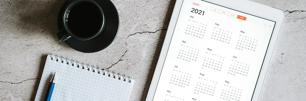 A tablet with an open calendar for 2021 year, a cup of coffee, and a spring notebook with a pen on a gray concrete background. banner Premium Photo