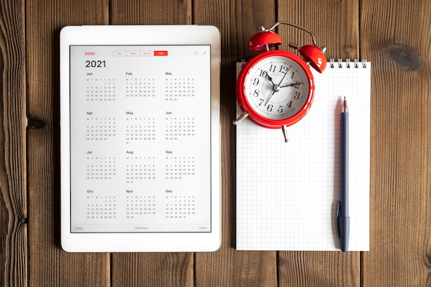 A tablet with an open calendar for 2021 year, a red alarm clock, and a spring notebook with a pen on a wooden boards table background Premium Photo