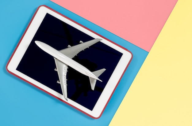 Tablet with plane for travel concept on blue yellow pink Premium Photo
