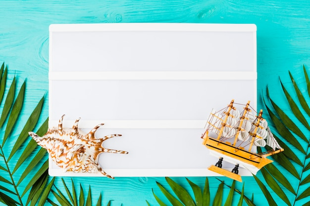 Tablet with plant leaves near toy boat and seashell Free Photo