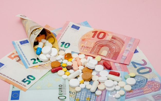 Tablets wrapped in euro with euro banknotes on a pink background. Premium Photo