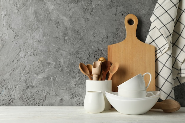 Tableware, cutlery and wooden board on white table against gray background, space for text Premium Photo
