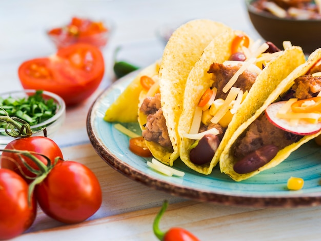 Taco on plate near tomatoes Free Photo