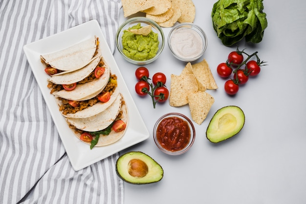 Tacos on dish among napkin near vegetables and sauces Free Photo