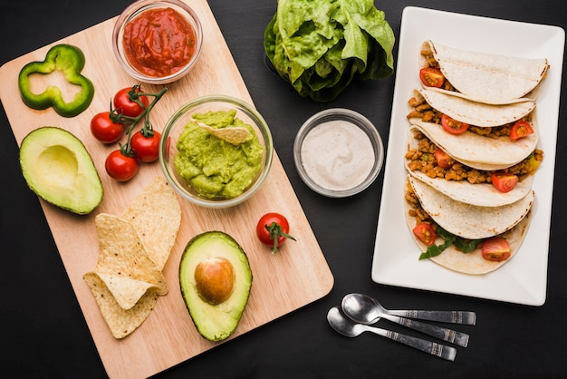 Tacos on plate near cutting board with vegetables and sauces Free Photo