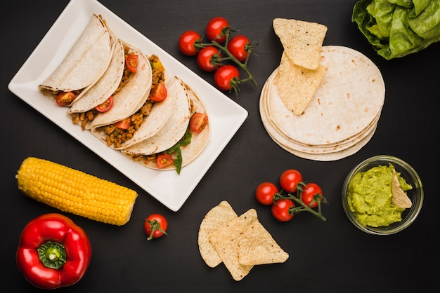 Tacos on plate near vegetables and sauce Free Photo