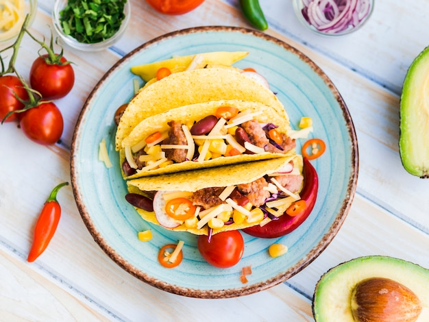 Tacos on plate near vegetables Free Photo
