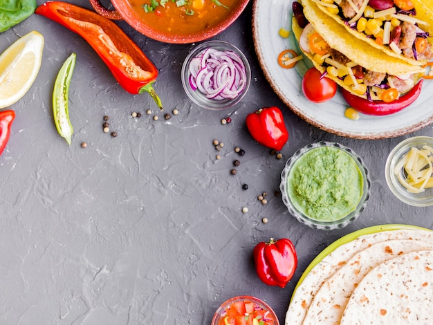 Tacos and quesadilla near cups with vegetables Free Photo