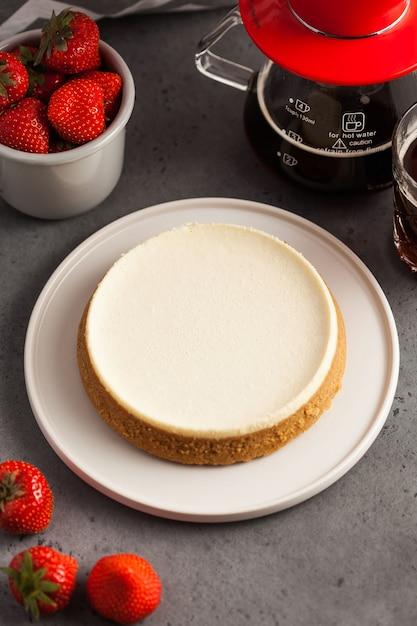 丸皿にココナッツチーズケーキ。ブラックコーヒーと新鮮なイチゴのマグカップとtaeapot。 Premium写真
