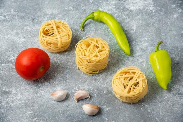 タリアテッレの生パスタの巣と野菜を大理石のテーブルに。 無料写真
