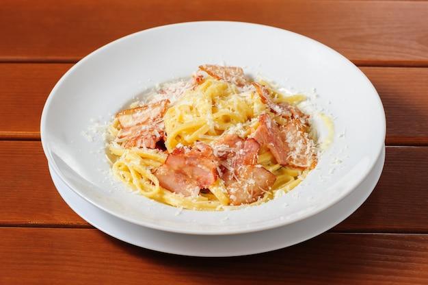 Tagliatelli carbanara italian cuisine on plate rustic kitchen table background Premium Photo