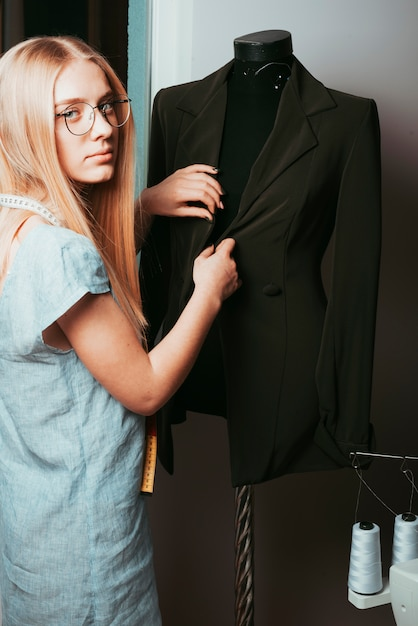 Tailor touching jacket on mannequin Free Photo