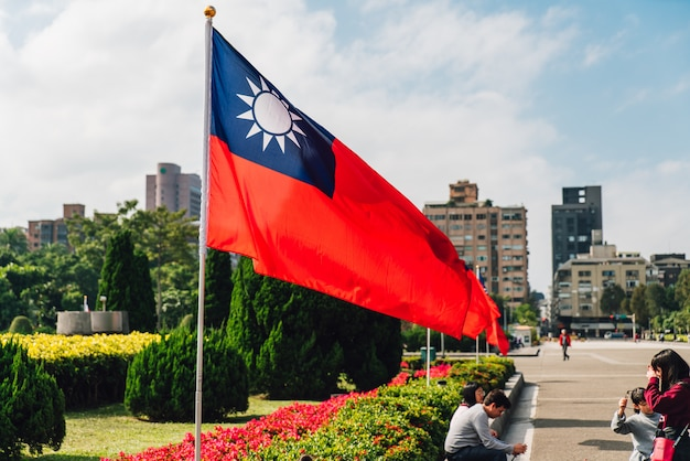 Taiwan national flag waving in the wind with tourists. Premium Photo