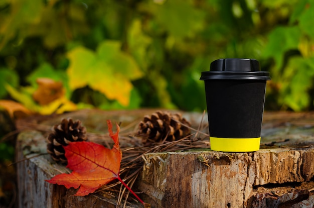 Take away black coffee cup with lid on stump in autumn park background. copy space, mock up Premium Photo