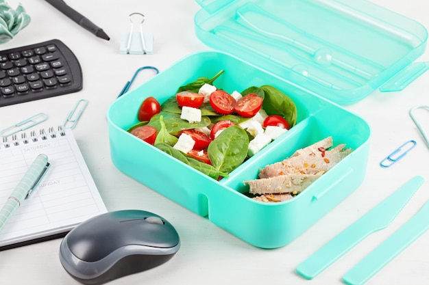 Take away lunch box with fresh salad and tuna fish over the office desk with office supplies. Premium Photo