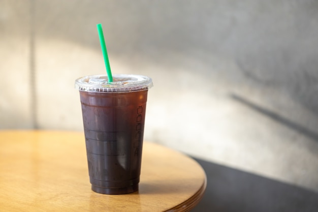 Take away plastic cup of iced black coffee americano on wooden ...