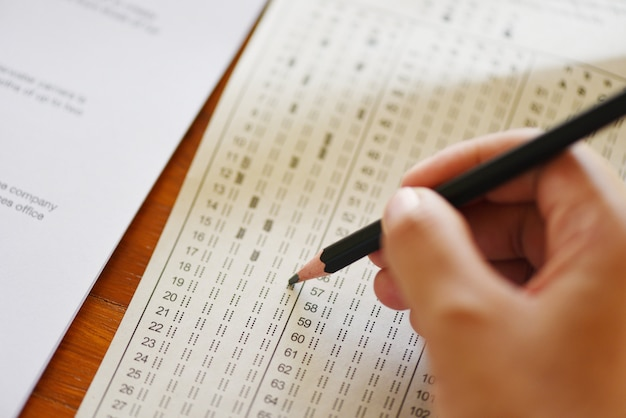 Take the exam final high school hand student holding pencil writing on paper answer sheet. Premium Photo