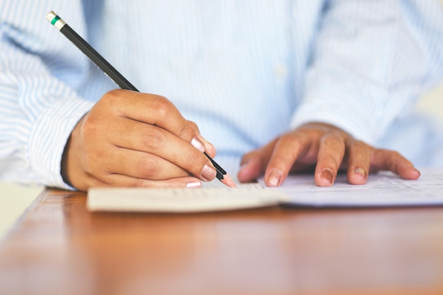 Take the exam final high school university student holding pencil writing on paper answer sheet Premium Photo