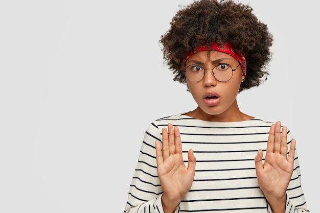 Забери это от меня! недовольная темнокожая девушка тянет ладони в стоп-жесте, чувствует себя несчастной Бесплатные Фотографии