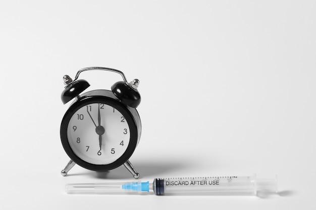 Принимайте лекарства вовремя. шприц и будильник на белой стене. время вакцинации. профилактика иммунизации от болезней. Premium Фотографии