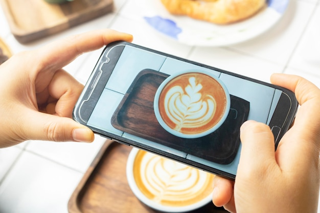 Take photo latte coffee with mobile phone Premium Photo