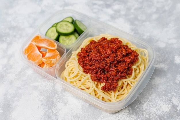 Takeaway spaghetti bolognaise in a plastic lunch box with detox drink and fruit slice on light Free Photo