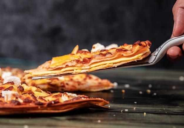 黒のピザのスライスを取る 無料写真