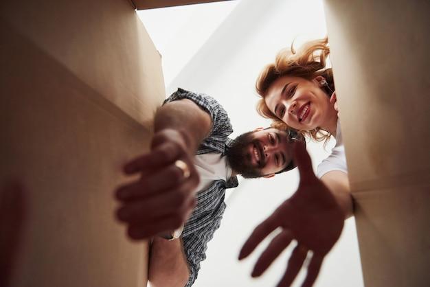 Достаем одежду из ящика. счастливая пара вместе в своем новом доме. концепция переезда Бесплатные Фотографии