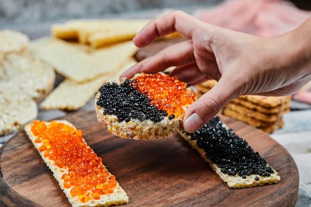 Prendendo un panino con cracker con caviale rosso e nero. Foto Gratuite