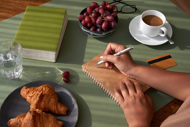 Taking notes at breakfast Free Photo