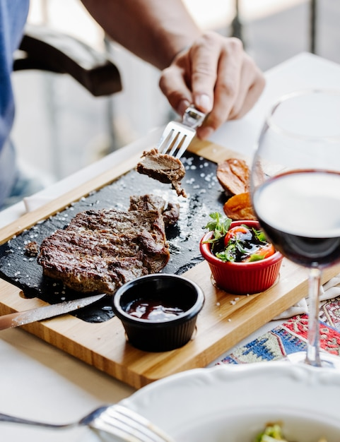 Taking a piece of steak with fork. Free Photo