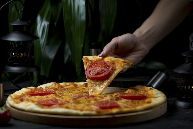 Taking a slice of margarita pizza with tomato slices Free Photo
