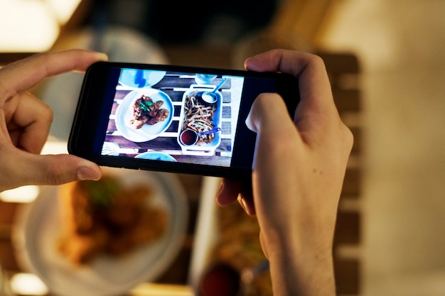 Taking smartphone photo of a dinner plate social media concept Free Photo