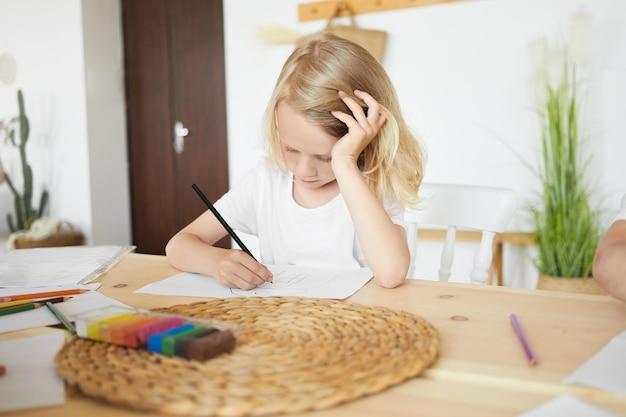家で楽しい時間を過ごし、頭を手に置いてテーブルに座って、絵を描いたり、スケッチしたり、黒鉛筆を使ったりする才能のある金髪のヨーロッパの少年。木製の机に集中した男子生徒の着色 無料写真