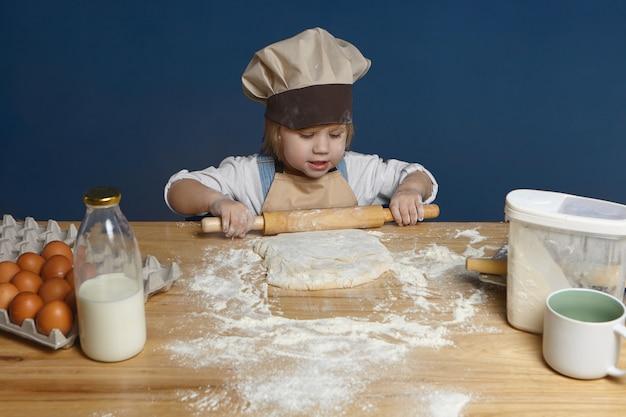 Bambina affascinante e talentuosa in cappello da chef e grembiule usando il mattarello mentre si impasta la pasta per la pizza fatta in casa. concetto di infanzia Foto Gratuite