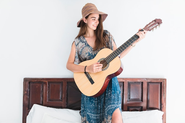 Talented teenage girl standing on bed playing guitar Free Photo